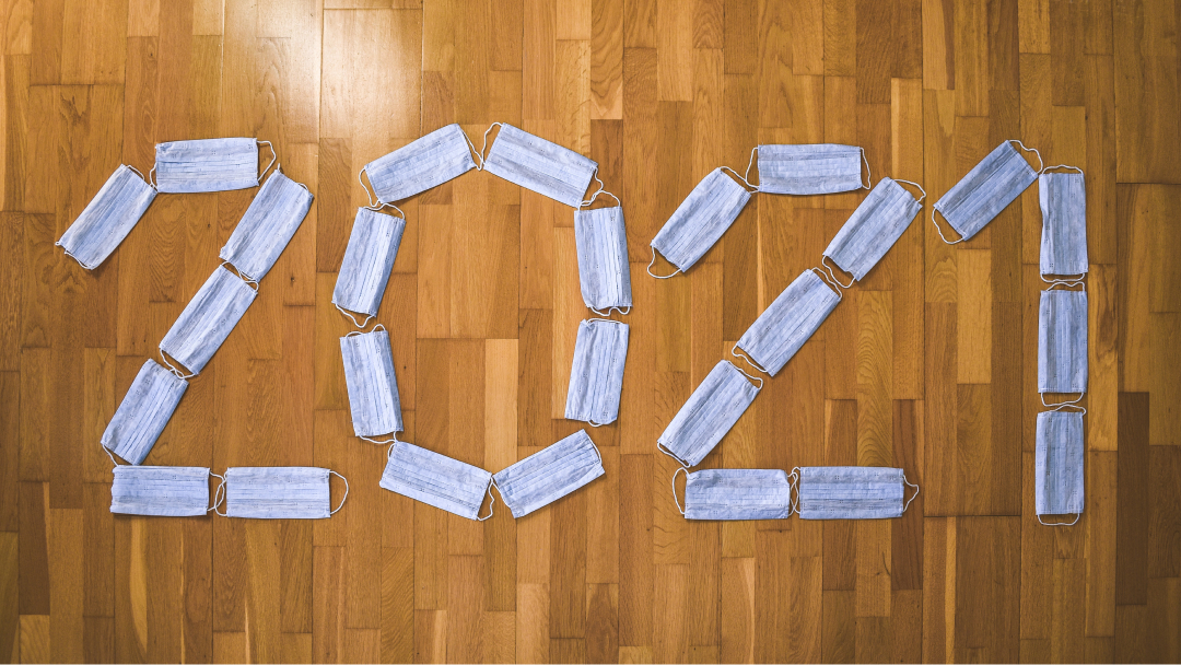 Protective masks arranged on the floor to form the word 2021.