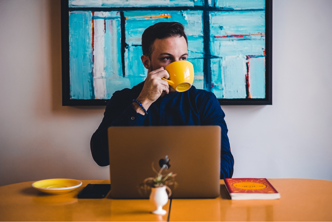 A man drinks coffee in front of his laptop in a coffee shop