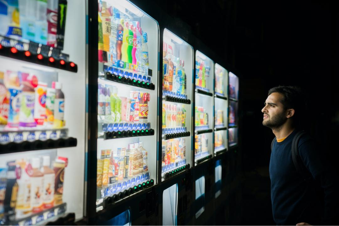 Un homme hésite devant plusieurs distributeurs de boissons