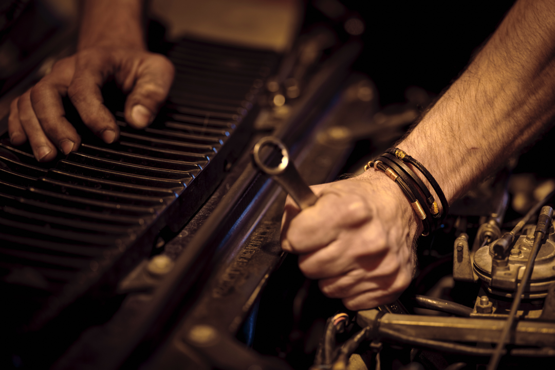 Mechanic working on a machine with a spanner